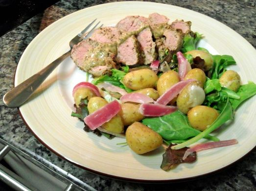 Mustard and Black Pepper Pork Loin with a salad of mixed greens, fingerling potatoes and blanched red onion.