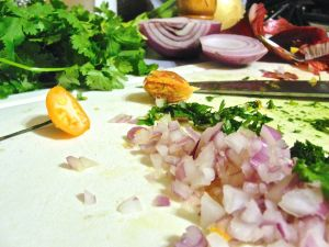 Preparing the salsa: fresh habanero, red onion, and cilantro.