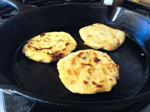 Cooking pupusas in an oiled pan.