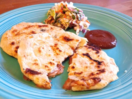 Pupusas with cabbage slaw and sauce.