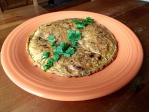 An Indian omelette topped with coriander leaf.