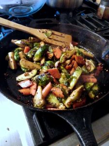 Stir frying the Brussels sprouts, carrot, and fresh ginger in mustard seed and oil.