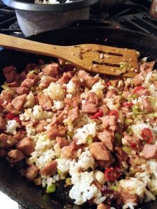 Stir frying the ham, garlic, spring onion, red pepper, and rice.