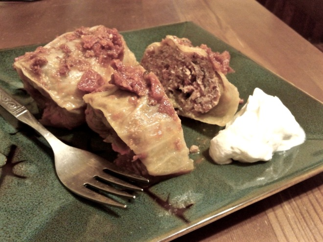 Gołąbki with tomato sauce, served with sour cream.